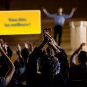 Public applaudissant le présentateur lors d'une convention ou d'un séminaire